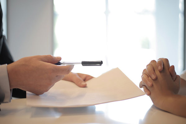 person handing another person a contract